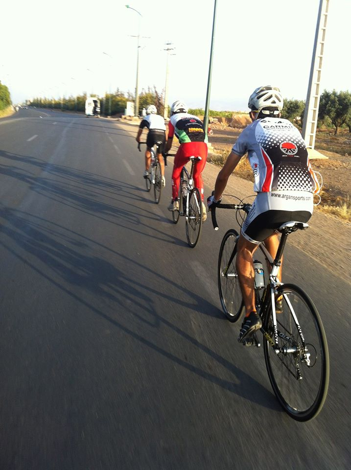 On road multi day tour photo of 3 riders on road bikes on a smooth road in Marrakech