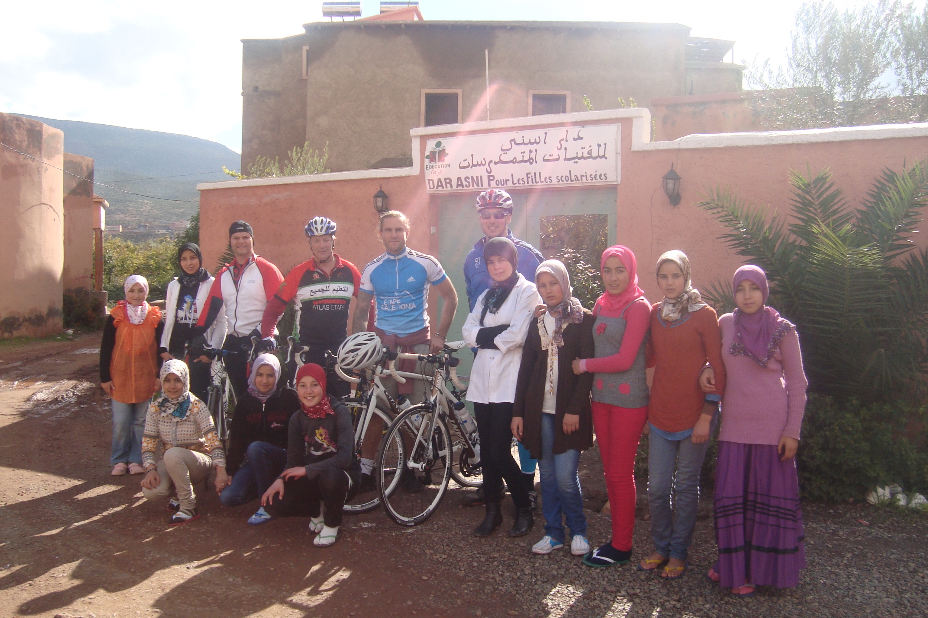 Picture of girl students together with Argan Sports bike riders who contributed to their education
