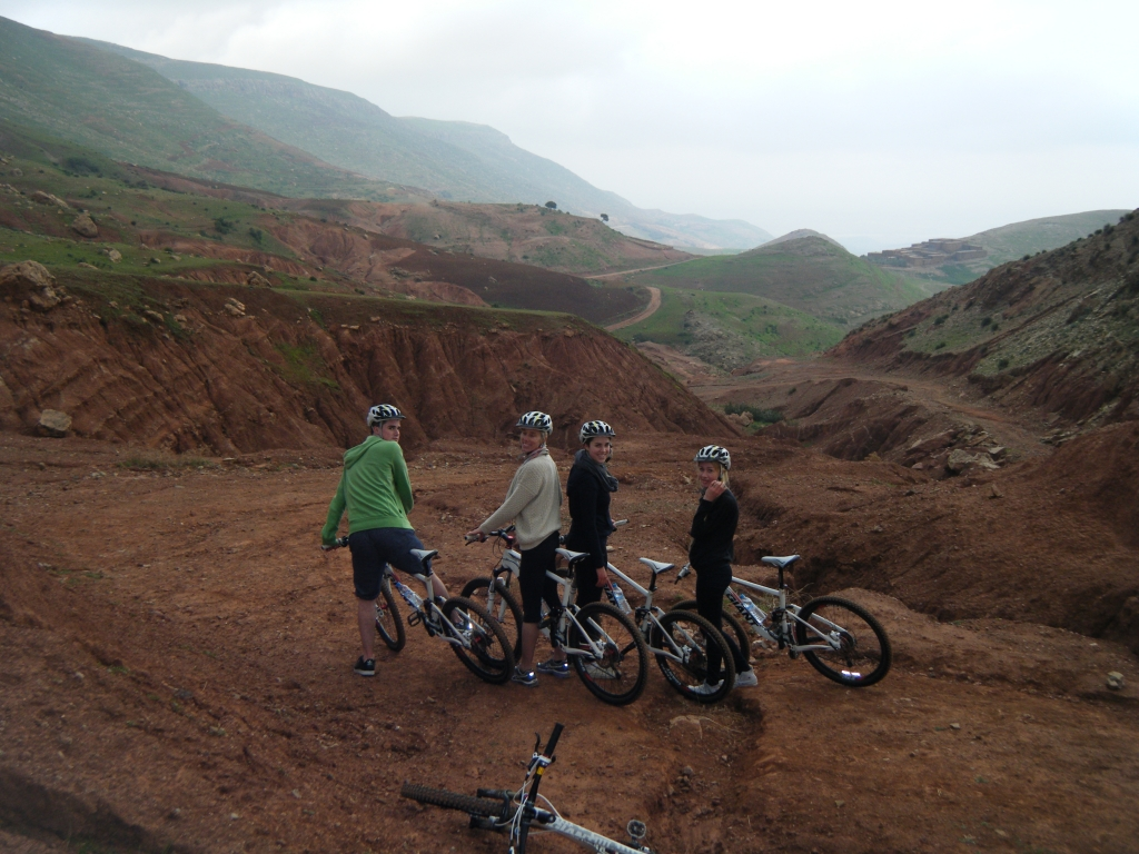 Picture of 4 people on tour with Argan Sports and their bikes with the Atlas Mountain trail stretching ahead in the foreground