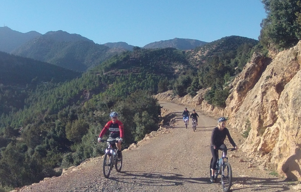 Argan Sports Photo of 4 MTB riders on a flat gravel road cutting through the Atlas Mountains