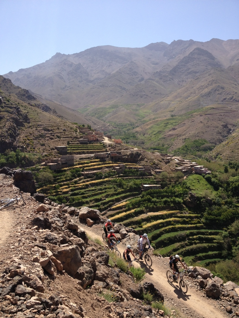 Photo of 5 mountain bikers with Argan Sports passing through terraced mountains in the High Atlas near Marrakech Morocco