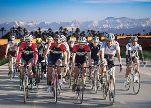 Photo of a group of AXS riders with the snow covered Atlas Mountains behind