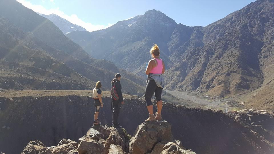 Photo of three trekkers on rocks in the atlas mountains