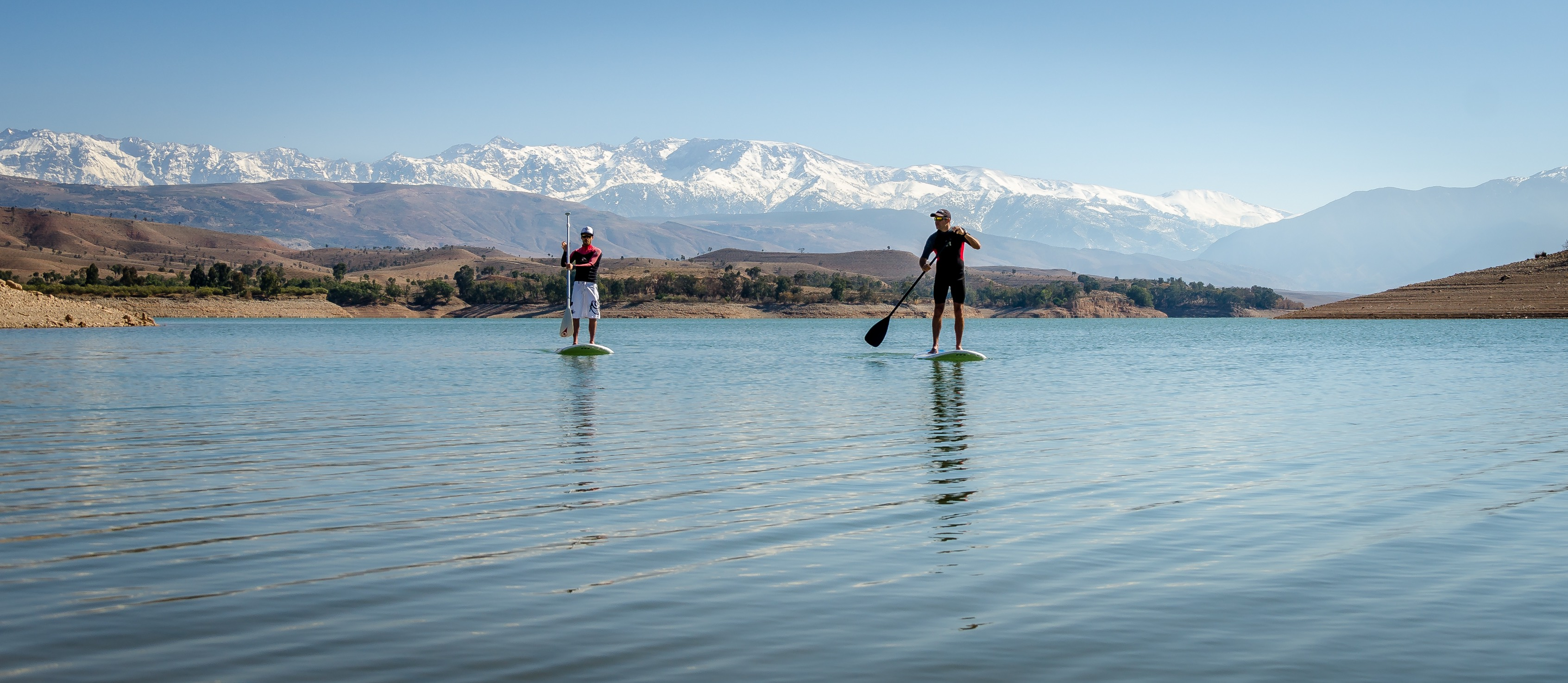 picture of two people paddle boarding with mountains in the background