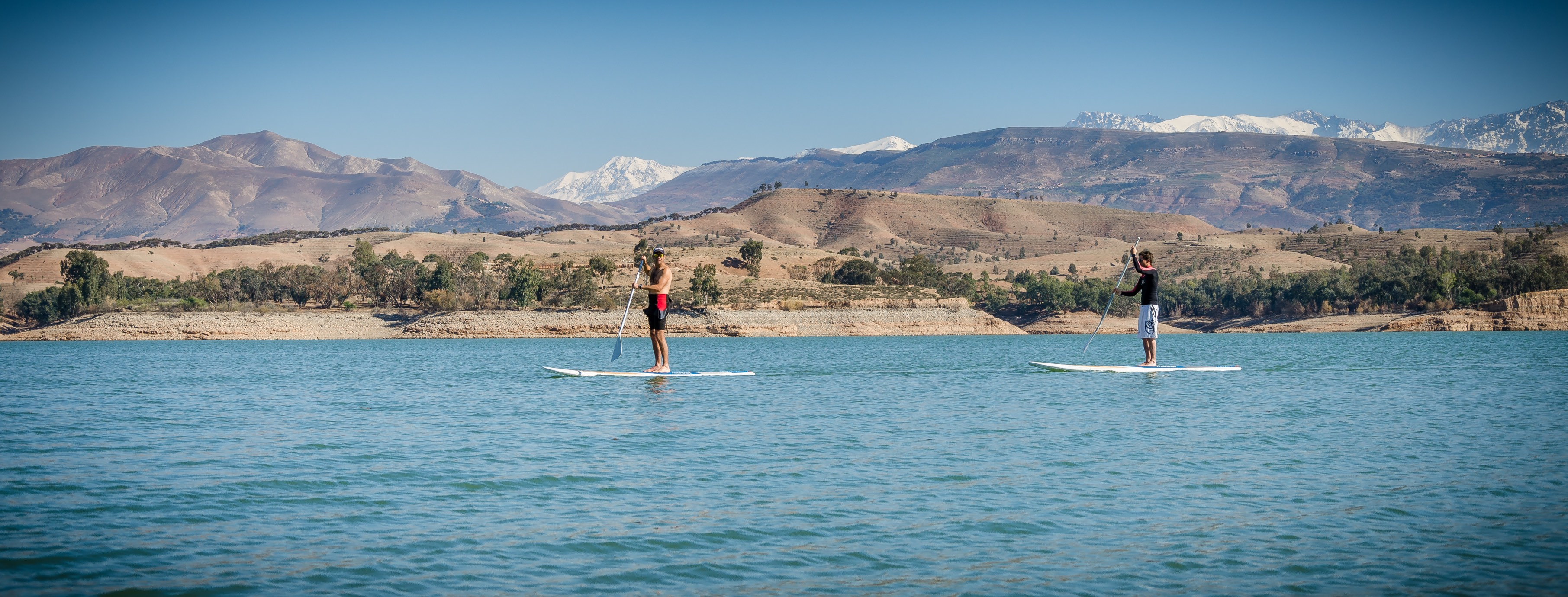 picture of two people kyaking with the montains in the background